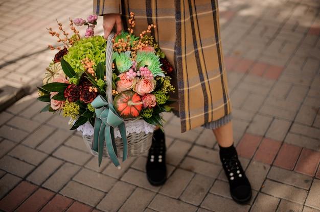 Donna in elegante cappotto a quadri in possesso di un grande cesto di vimini di bella composizione autunnale di fiori