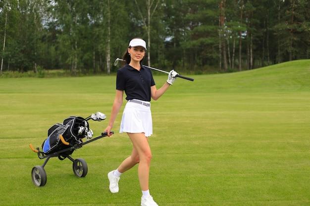 Donna in abito da golf estivo alla moda che cammina con una borsa di autisti su un bellissimo campo verde per il gioco del golf.