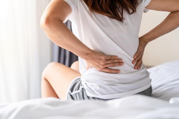 Donna che soffre di mal di schiena sul letto, assistenza sanitaria e concetto di problema