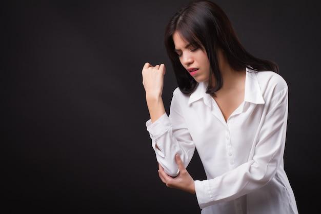 Donna che soffre di dolori articolari del gomito, artrite reumatoide o gotta