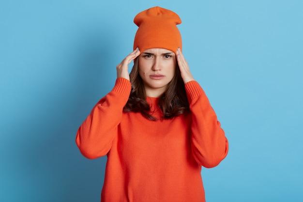 La donna soffre di mal di testa, tocca le tempie con entrambe le mani, ha emicrania, indossa un maglione e un cappello arancione casual, ha bisogno di cure, assistenza sanitaria, posa isolata su un muro blu.