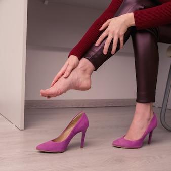 La donna che soffre di dolori alle gambe in ufficio