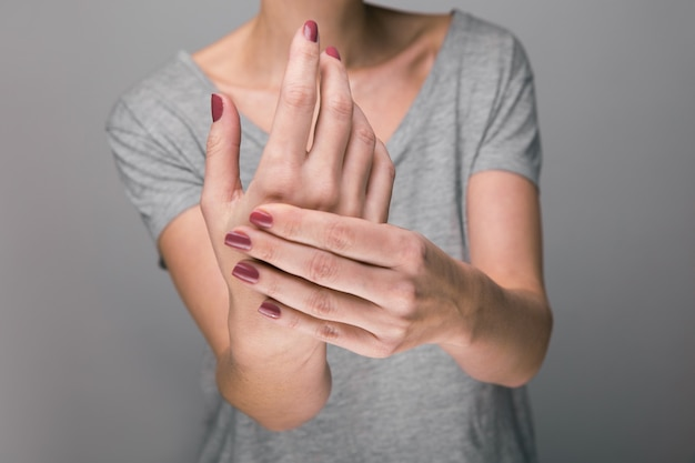 Donna che soffre di dolore osseo su sfondo grigio, concetto con smorfia di artrite della mano nel dolore