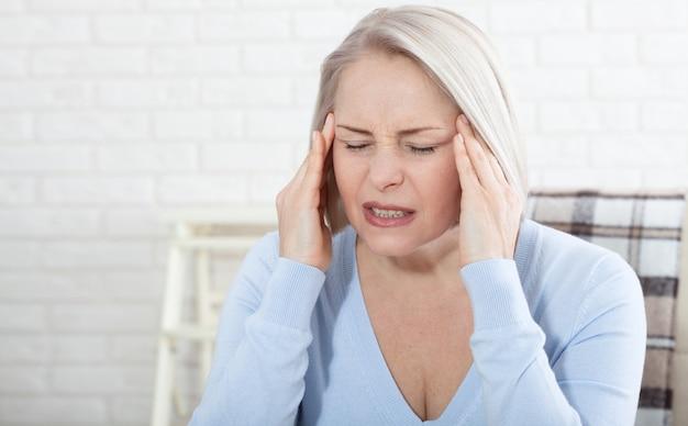 Donna che soffre di stress o mal di testa che fa smorfie di dolore mentre tiene la parte posteriore del collo