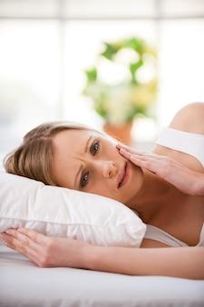 Donna che soffre di mal di denti. giovane donna frustrata che si tocca la guancia e guarda la telecamera mentre sta in piedi isolata su bianco