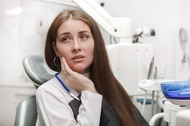 La donna che soffre di mal di denti, seduto in poltrona odontoiatrica presso la clinica