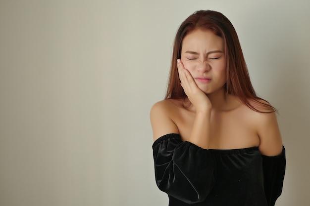 Donna che soffre di mal di denti, carie, sensibilità