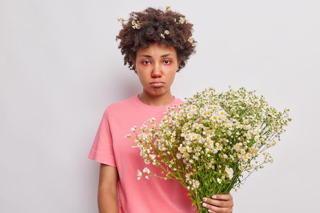 La donna soffre di sintomi allergici tiene il bouquet di camomilla ha gli occhi gonfi rossi borse il labbro inferiore indossa una maglietta rosa casual isolata su bianco