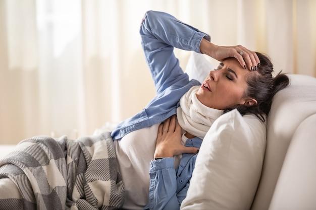 La donna soffre di sintomi come dolore ai polmoni e mal di testa mentre riposa sul divano di casa.