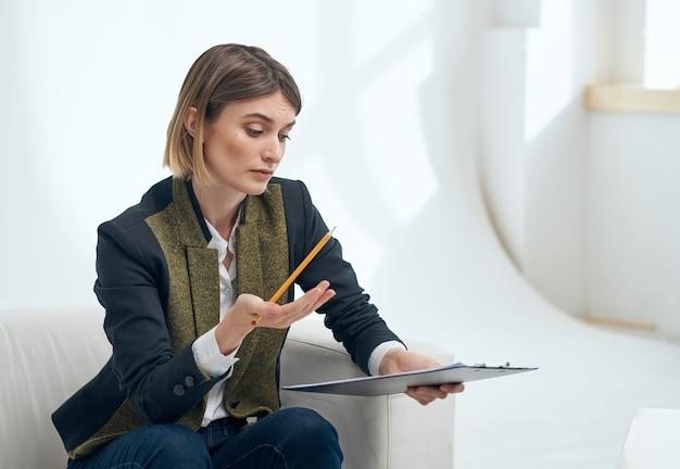 Donna in un vestito seduto su una sedia documenti. foto di alta qualità