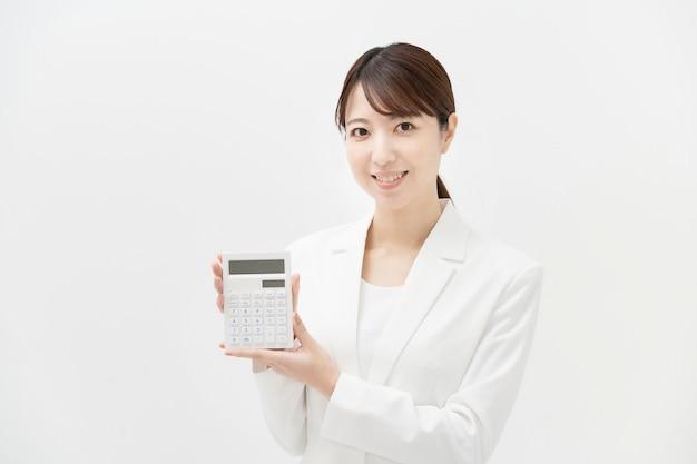 Una donna in un vestito con una calcolatrice e uno sfondo bianco
