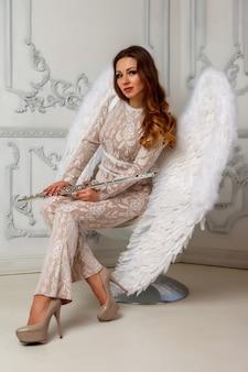 Donna in vestito con le ali con flauto su sfondo chiaro con texture