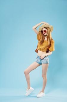 La donna in abiti estivi cappello occhiali da sole viaggia a figura intera