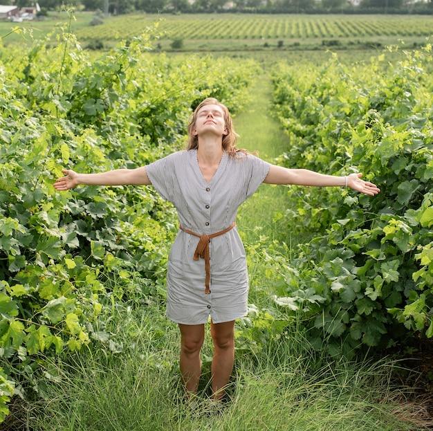 Donna in abito estivo che cammina attraverso la vigna annusando l'uva guardando il cielo,