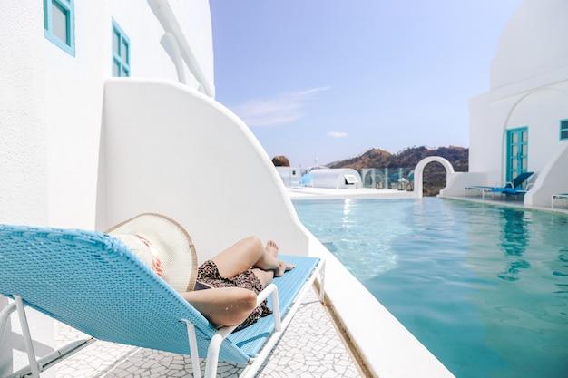 Donna in cappello estivo sdraiato su una sedia rilassante per prendere il sole in piscina