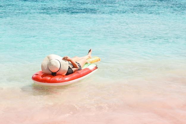 Donna in cappello estivo sdraiato su un materasso ad acqua gonfiabile in spiaggia di sabbia rosa a labuan bajo