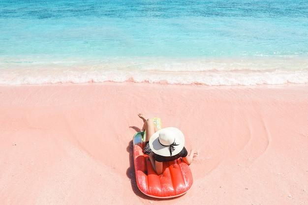Donna in cappello estivo che si rilassa su un gonfiabile in spiaggia di sabbia rosa a labuan bajo