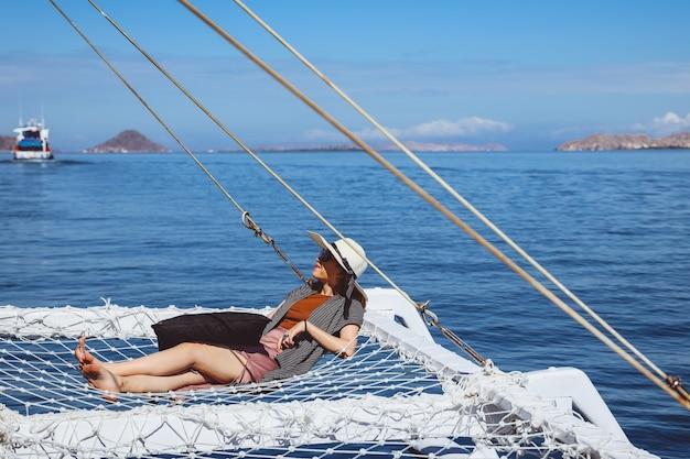 Donna in cappello estivo e occhiali da sole che si rilassano sulla rete del catamarano godendosi la vista sul mare