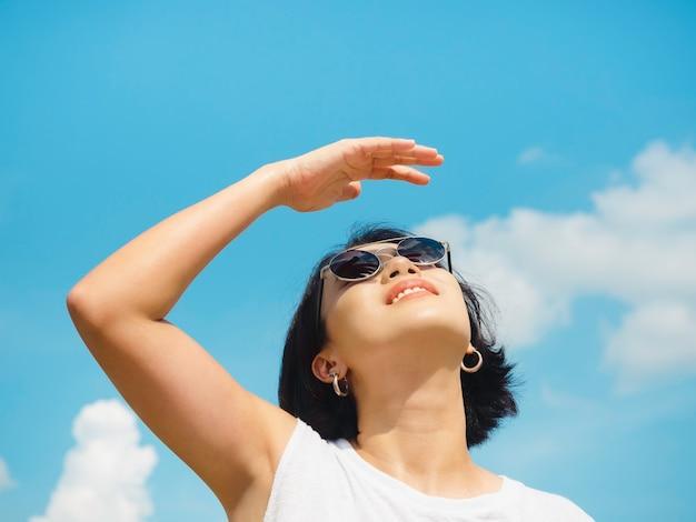 Donna in estate. sorridente bella donna asiatica capelli corti indossando occhiali da sole e camicia bianca senza maniche guardando in alto e ombreggiatura occhi con la mano su sfondo blu cielo in giornata di sole in estate.