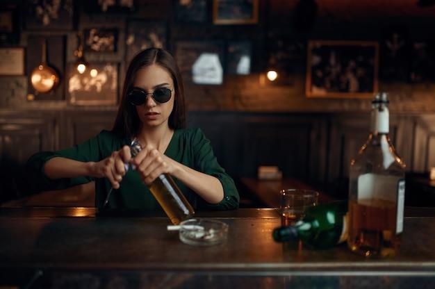 La donna in occhiali da sole apre una bottiglia di birra al bancone del bar. una donna in un pub, emozioni umane, attività ricreative, depressione