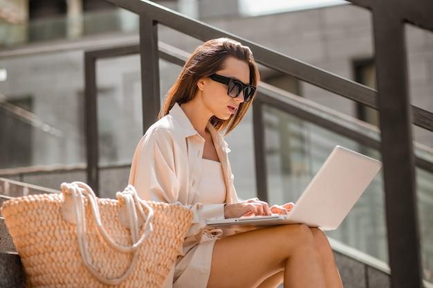 Una donna con gli occhiali da sole seduta sui gradini e al lavoro su un laptop