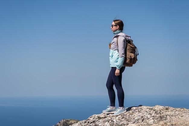 Una donna con gli occhiali da sole si trova su un'alta montagna e gode della vista dell'infinito punto di vista del mare blu