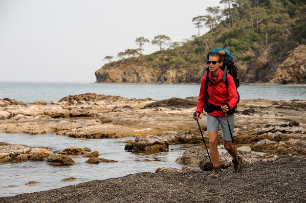 Donna in occhiali da sole che cammina sulle rocce sul mare con zaino escursionistico