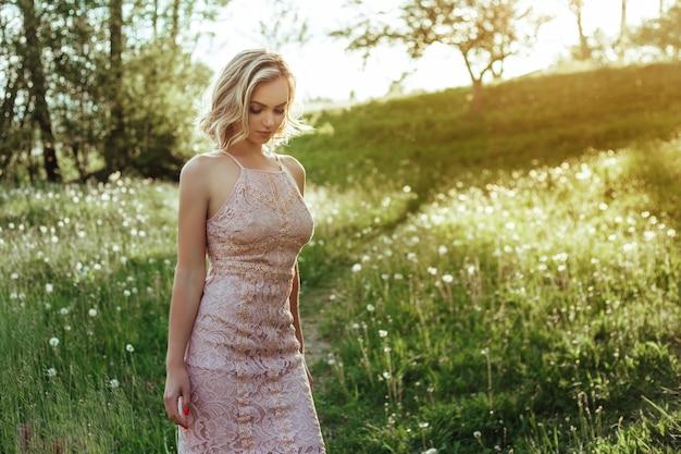 Una donna al tramonto in un campo di denti di leone in un vestito rosa