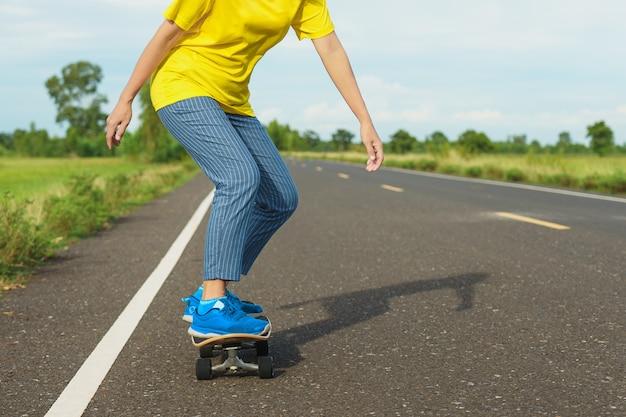 Donna su surf skate con strada in campagna