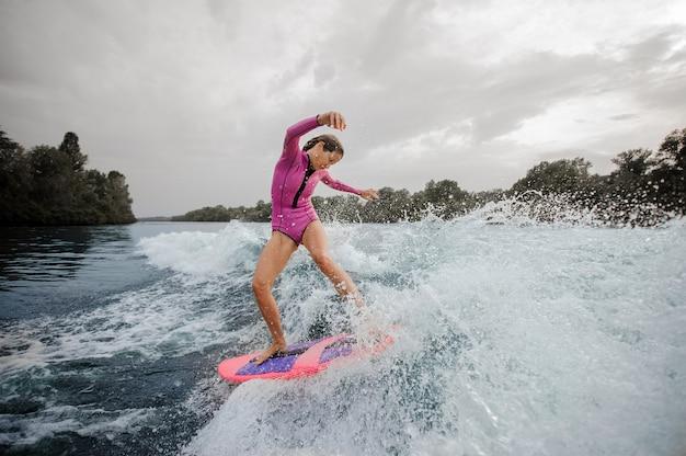 Surfista della donna che guida giù il fiume di spruzzatura blu contro il cielo