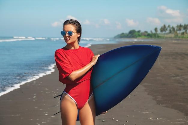 Surfista donna con shortboard sulla spiaggia
