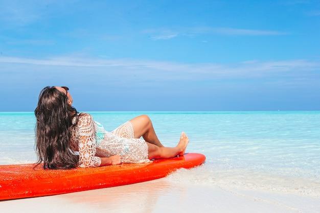Donna che surfa in mare in vacanza