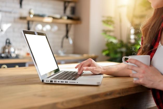 La donna naviga in internet con il suo laptop con uno schermo bianco. lavora a casa come smart working