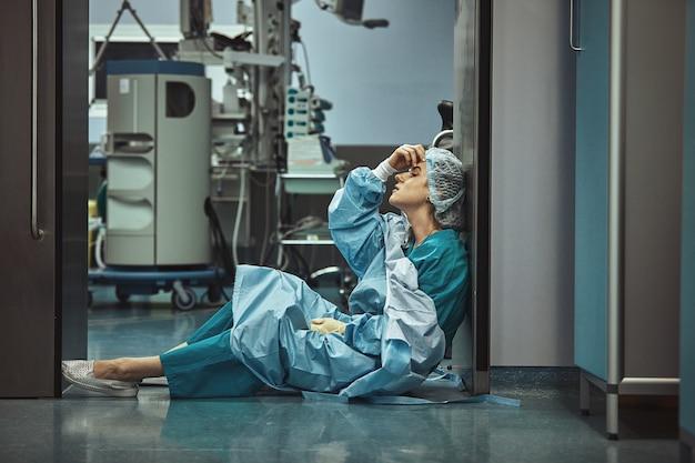 Chirurgo della donna che osserva affaticamento di tristezza dopo il problema infelice di senso di colpa di depressione di copyspace di intervento chirurgico