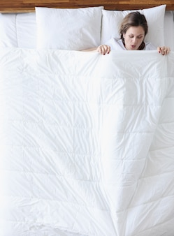 Donna sorpresa guardando sotto la coperta in vista dall'alto del letto. concetto di mestruazioni pesanti
