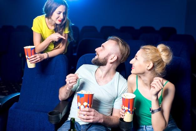 Donna che giura sulla coppia parlando ad alta voce sui sedili anteriori del cinema