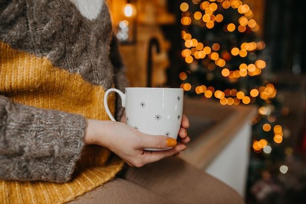 Donna in maglione, che tiene una tazza di caffè o tè su sfondo di luci di natale