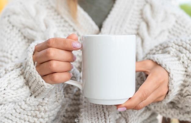 Donna in maglione che tiene una tazza di caffè