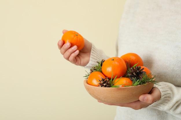 La donna in maglione tiene la ciotola con i mandarini, spazio per il testo