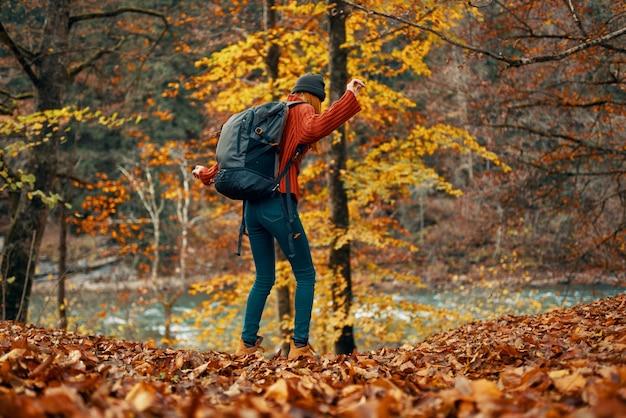 Donna in un maglione e jeans e stivali in autunno in un parco nella natura vicino al fiume