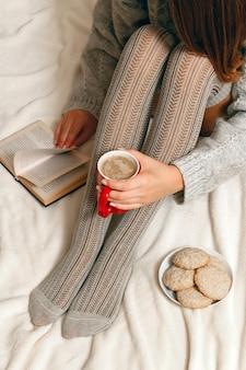 Donna in un maglione e calze rilassante a letto