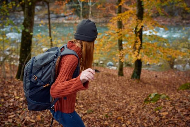 Donna in un maglione con uno zaino sulla schiena vicino al fiume in montagna e gli alberi del parco paesaggio autunnale