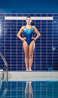 Nuotatore della donna che sta vicino allo stagno dell'interno pronto ad tuffarsi