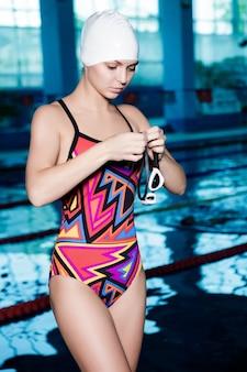 Il nuotatore della donna in una cuffia da nuoto veste gli occhiali e pronto a nuotare