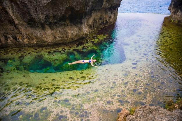 La donna che nuota nel billabong di angel è una piscina a sfioro naturale, nusa penida, bali