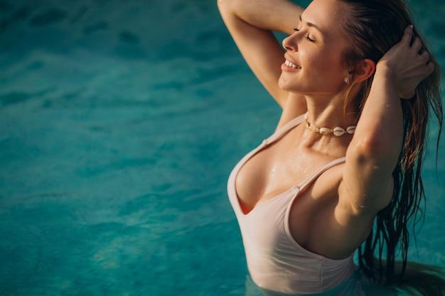 Donna che nuota nella piscina blu