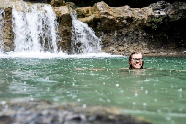 Donna che nuota nel fiume di montagna con una cascata