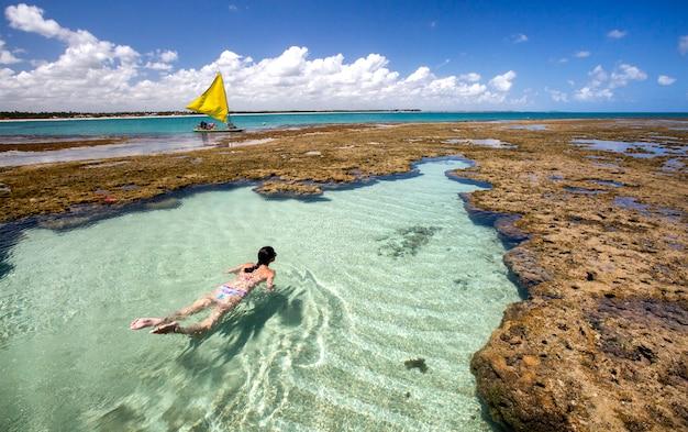 Donna nuotare e rilassarsi sulla piscina naturale di porto de galinhas, pernambuco - brasile. spiaggia brasiliana.