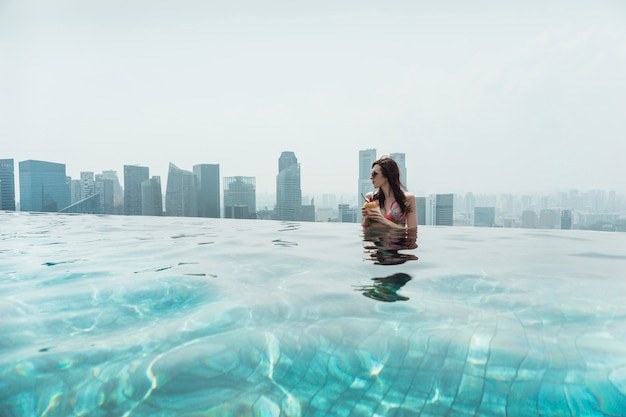 Donna che nuota nella piscina all'aperto sul tetto a singapore.una giovane donna con una noce di cocco in mano è rilassante nella piscina all'aperto sul tetto