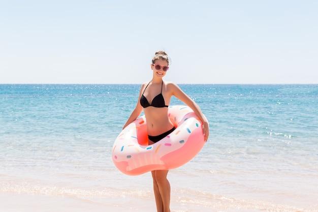 Donna che nuota con ciambella gonfiabile sulla spiaggia in giornata di sole estivo. vacanze estive e concetto di vacanza.